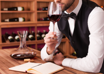 36586758 - sommelier examining wine. cropped image of confident male sommelier examining wine while smelling it and leaning at the wooden table with wine shelf in the background